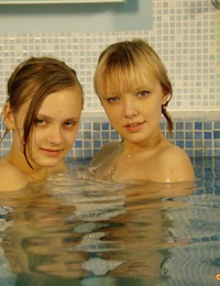 Two horny lesbian teenagers swimming together in a pool