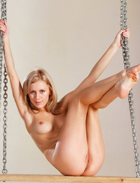 Tamara F: Pivoter by Alex Sironi - Tamara playfully poses on a swing, lifting her dress' skirt naughtily to flash her smootj, shaven pussy.